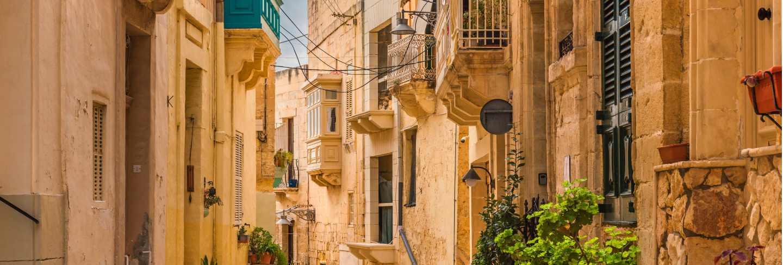 Old medieval street with yellow buildings, beautiful balconies and flower pots in birgu, valletta, malta Premium Photo
