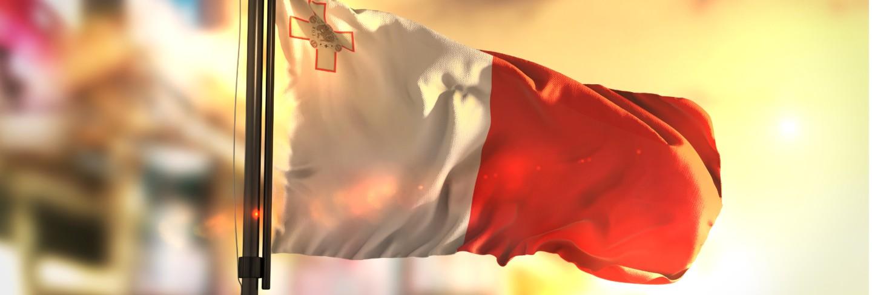 Malta flag against city blurred background at sunrise backlight Premium Photo