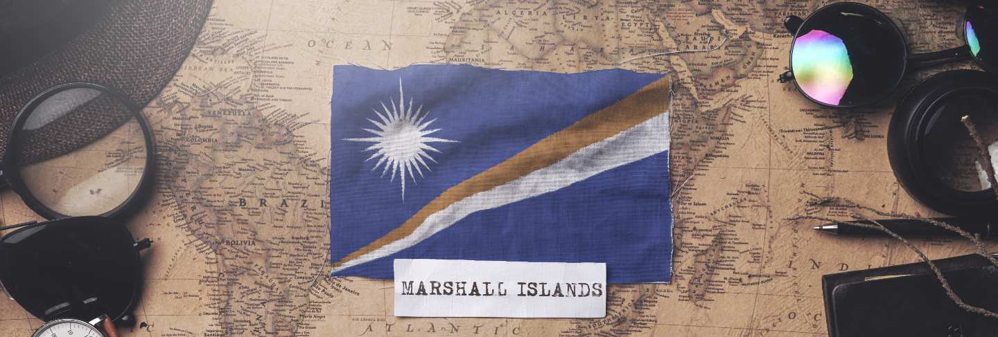 Marshall islands flag between traveler's accessories on old vintage map. overhead shot Premium Photo