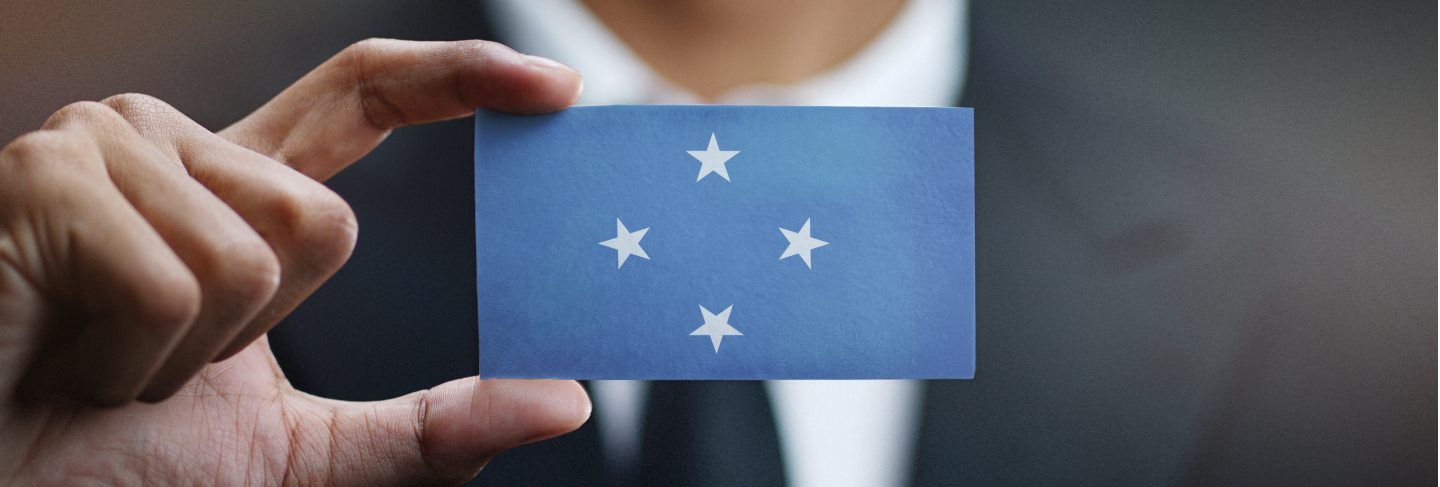 Businessman holding card of federated states of micronesia flag Premium Photo