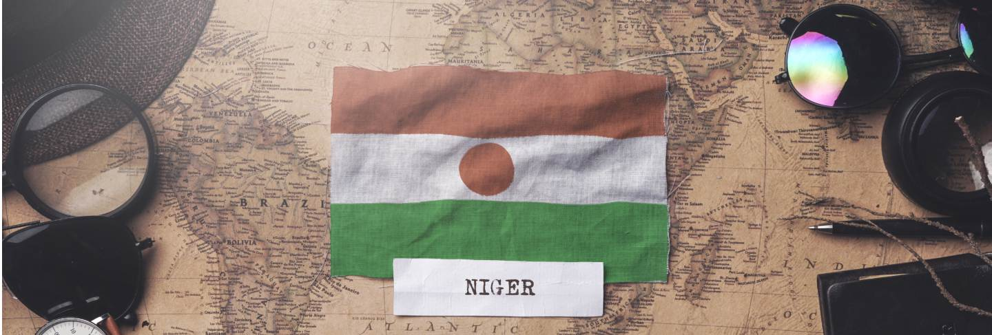 Niger flag between traveler's accessories on old vintage map. overhead shot