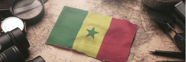 Senegal flag between traveler's accessories on old vintage map. tourist destination concept. Premium Photo