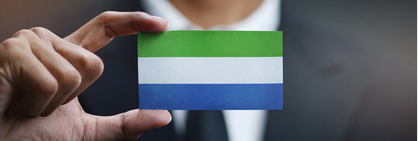 Businessman holding card of sierra leone flag