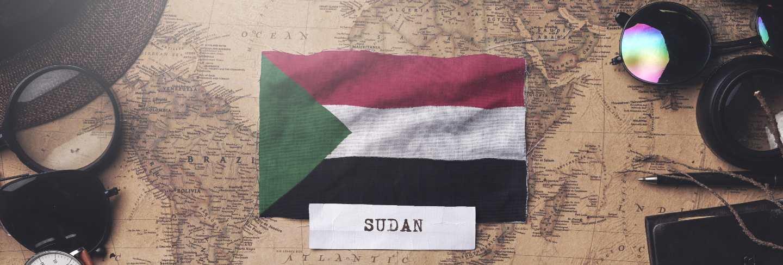 Sudan flag between traveler's accessories on old vintage map. overhead shot
