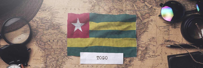 Togo flag between traveler's accessories on old vintage map. overhead shot