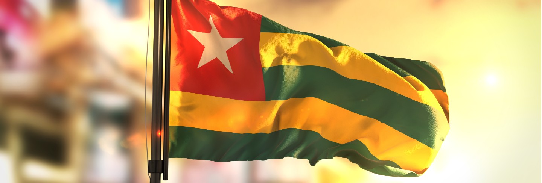 Togo flag against city blurred background at sunrise backlight