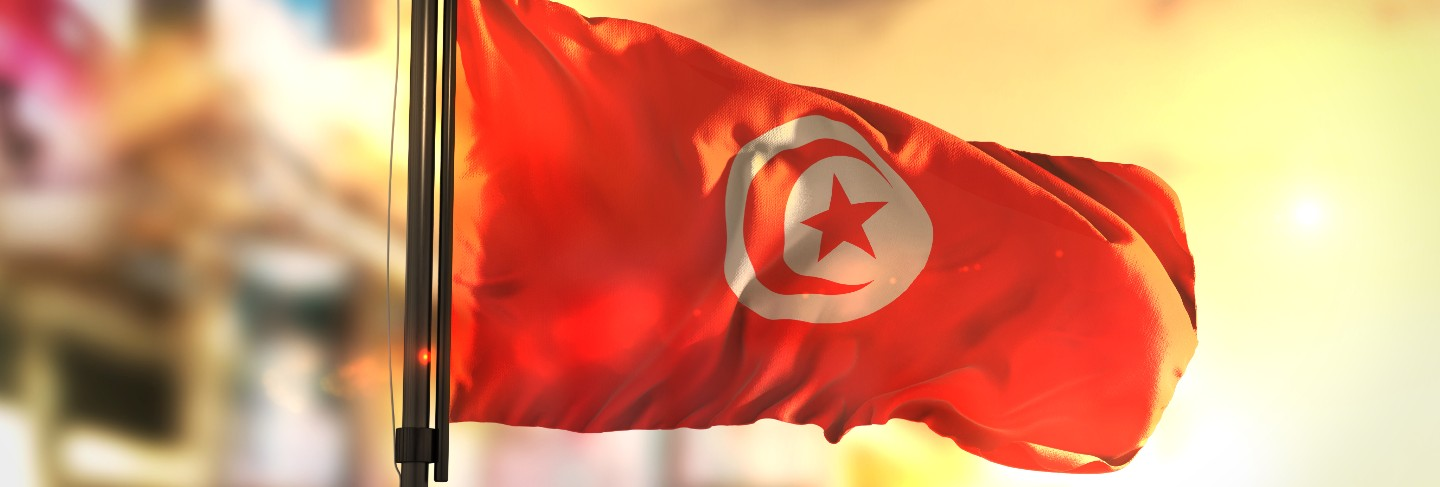 Tunisia flag against city blurred background at sunrise backlight