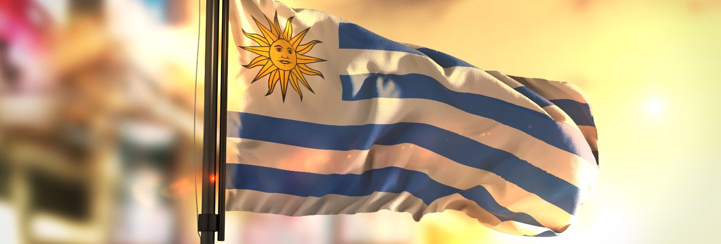 Uruguay flag against city blurred background at sunrise backlight