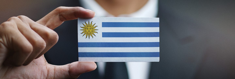 Businessman holding card of uruguay flag
