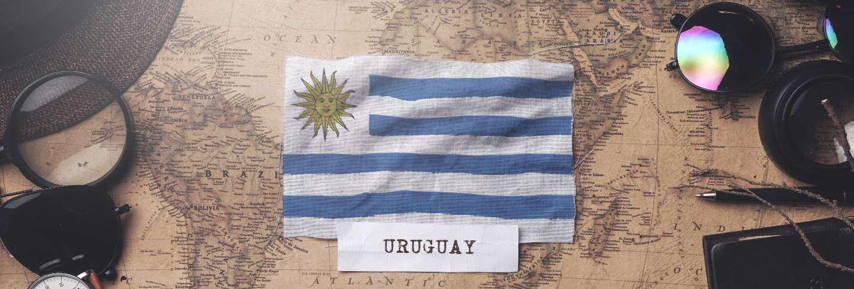 Uruguay flag between traveler's accessories on old vintage map