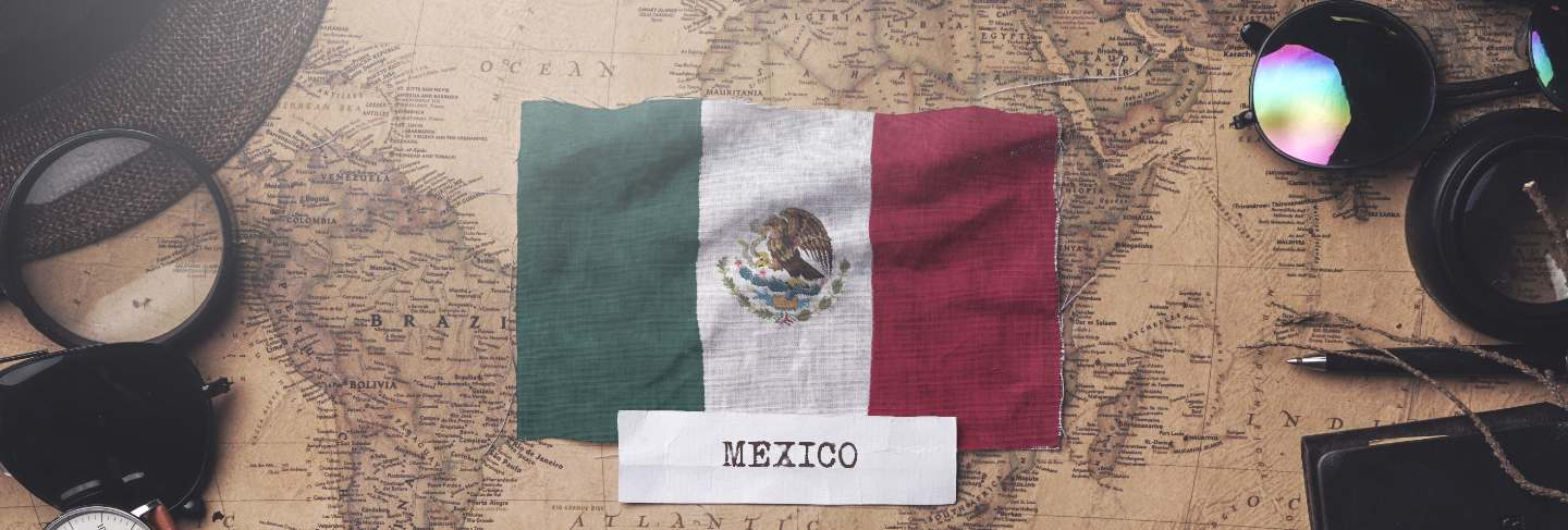Mexico flag between traveler's accessories on old vintage map. overhead shot