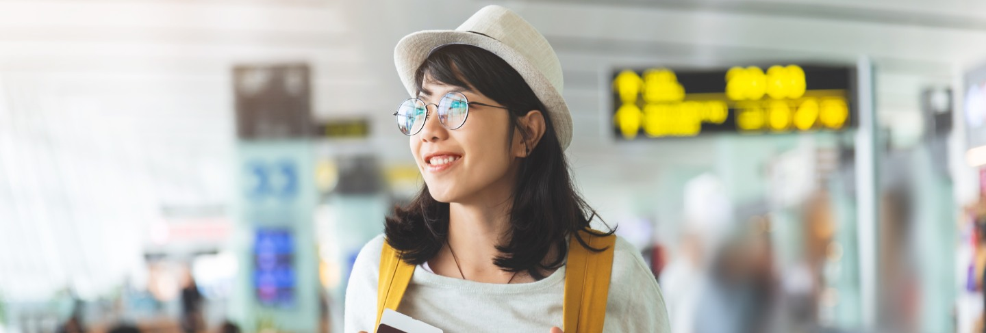 Asian woman wear glasses, hat with yellow backpack is holding flying ticket, passport at the hall of airport.