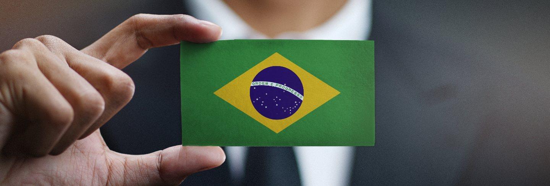 Businessman holding card of brazil flag