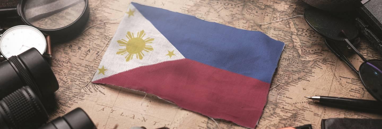 Philippines flag between traveler's accessories on old vintage map. tourist destination concept