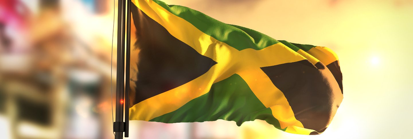 Jamaica flag against city blurred background at sunrise backlight