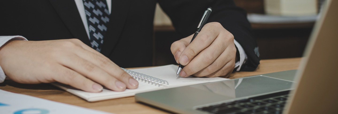 Attractive business man in black suit working and writing on document report on desk in meeting room at home office, investment, contract,
