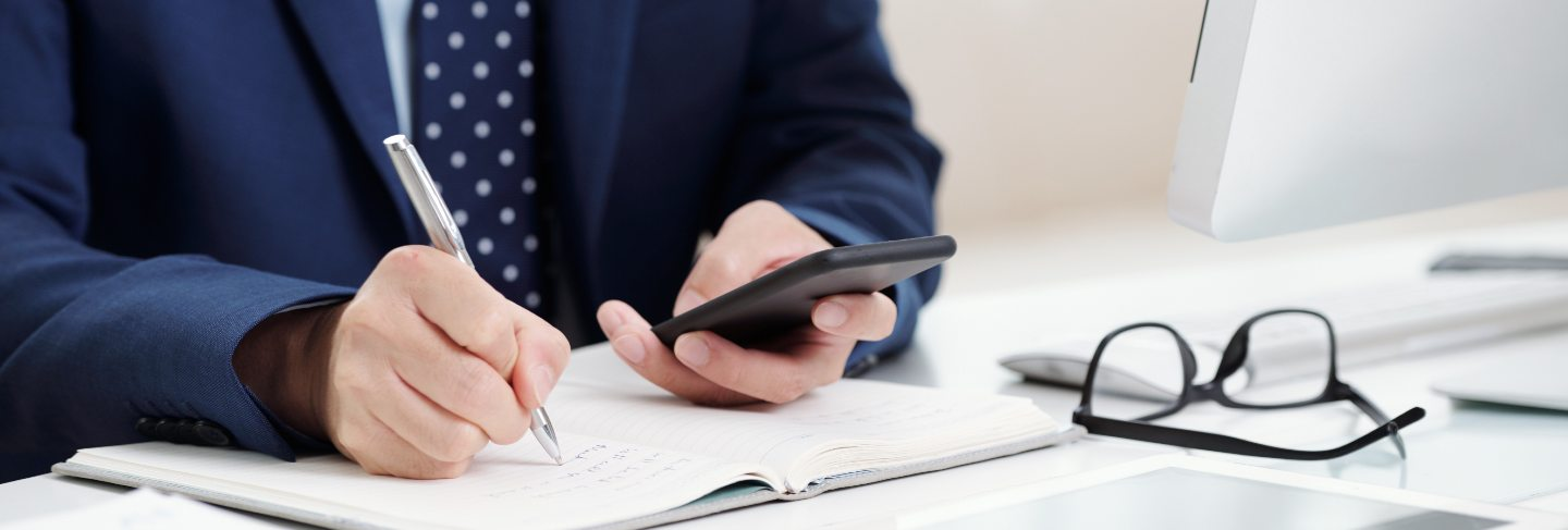 Cropped business man making notes from his smartphone calendar to the organizer