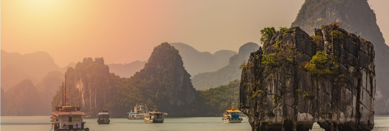Tourist junks floating among limestone rocks at ha long bay
