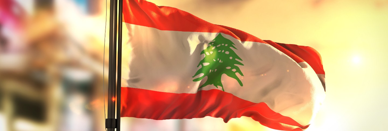 Lebanon flag against city blurred background at sunrise backlight