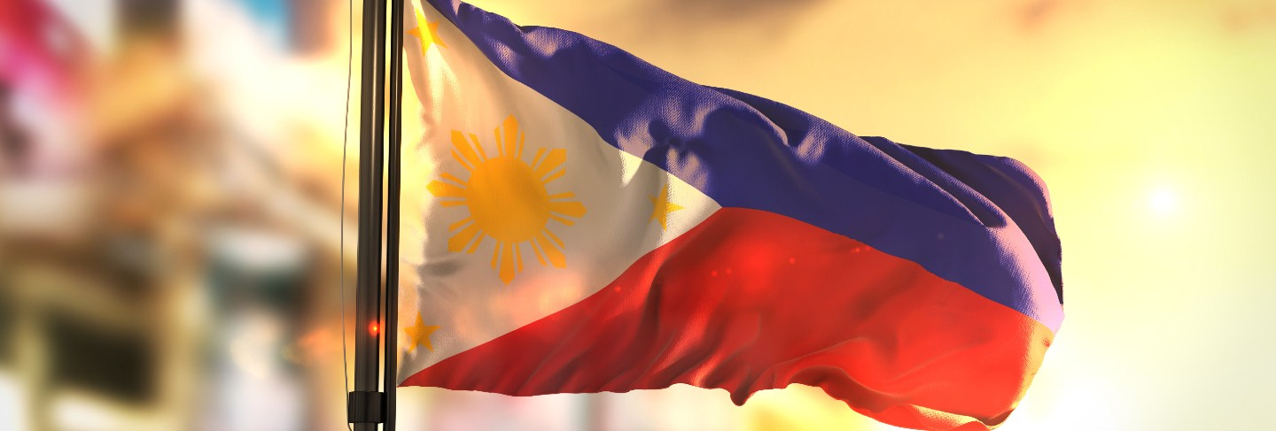 Philippines flag against city blurred background at sunrise backlight