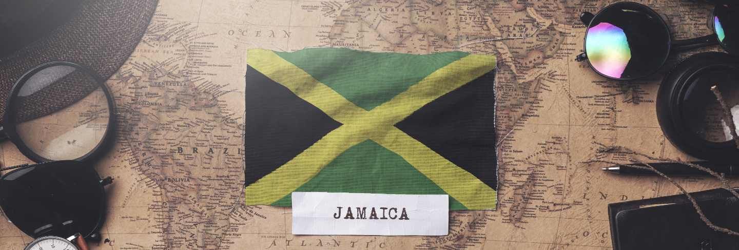 Jamaica flag between traveler's accessories on old vintage map. overhead shot