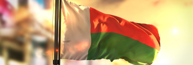 Madagascar flag against city blurred background at sunrise backlight