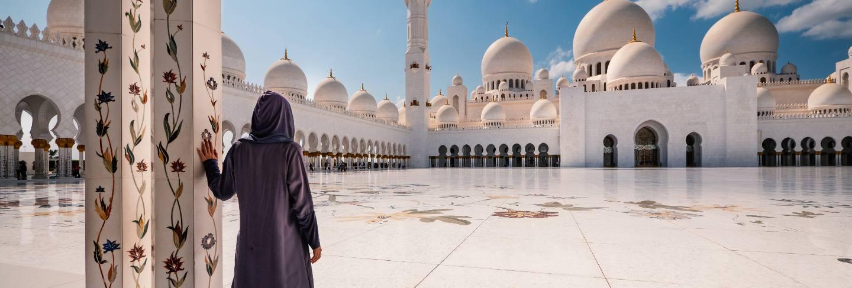 Woman with traditional dress inside sheikh zayed mosque. abu dhabi, united arab emirates.