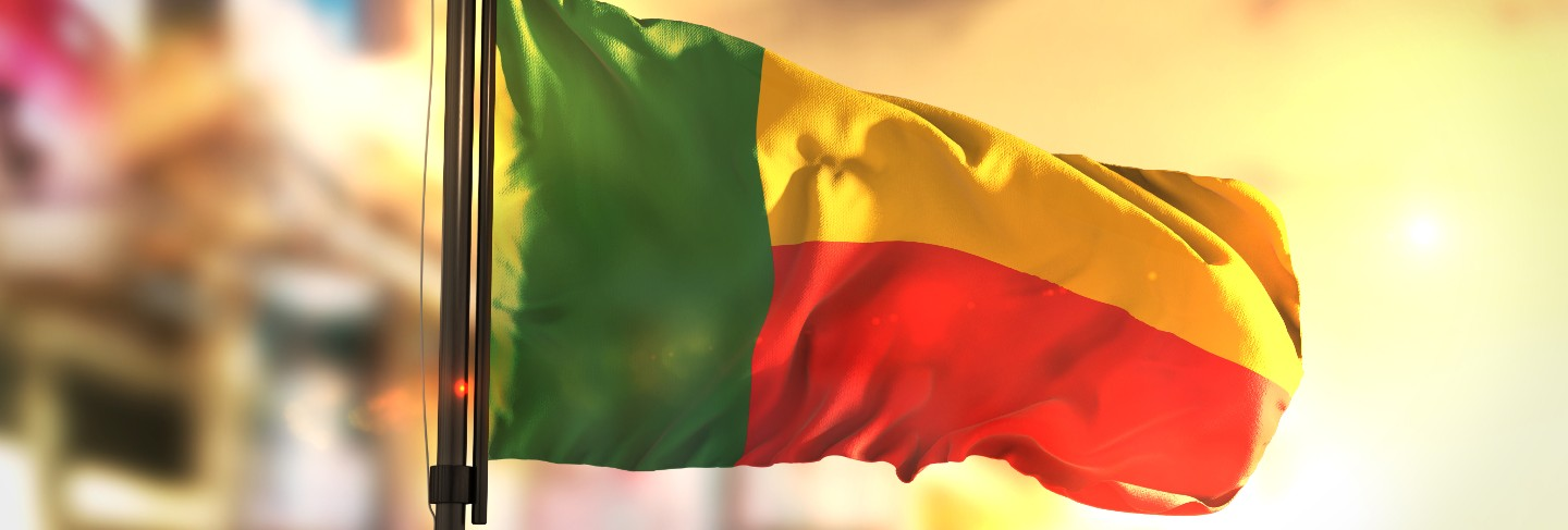 Benin flag against city blurred background at sunrise