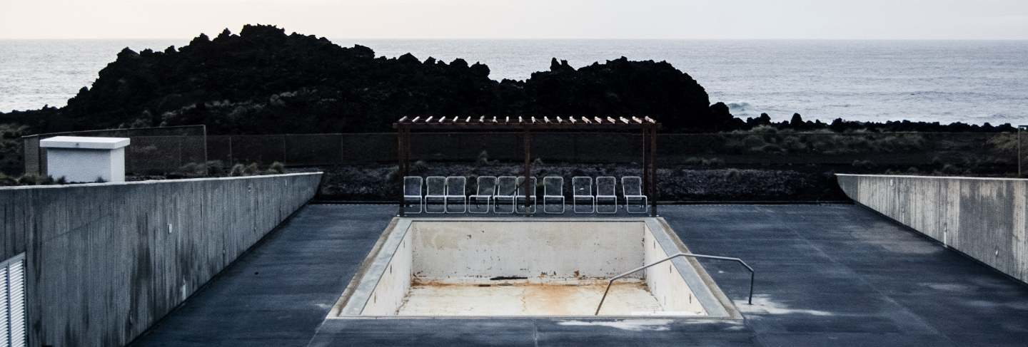 Empty pool with chairs near the cliff and a sea
