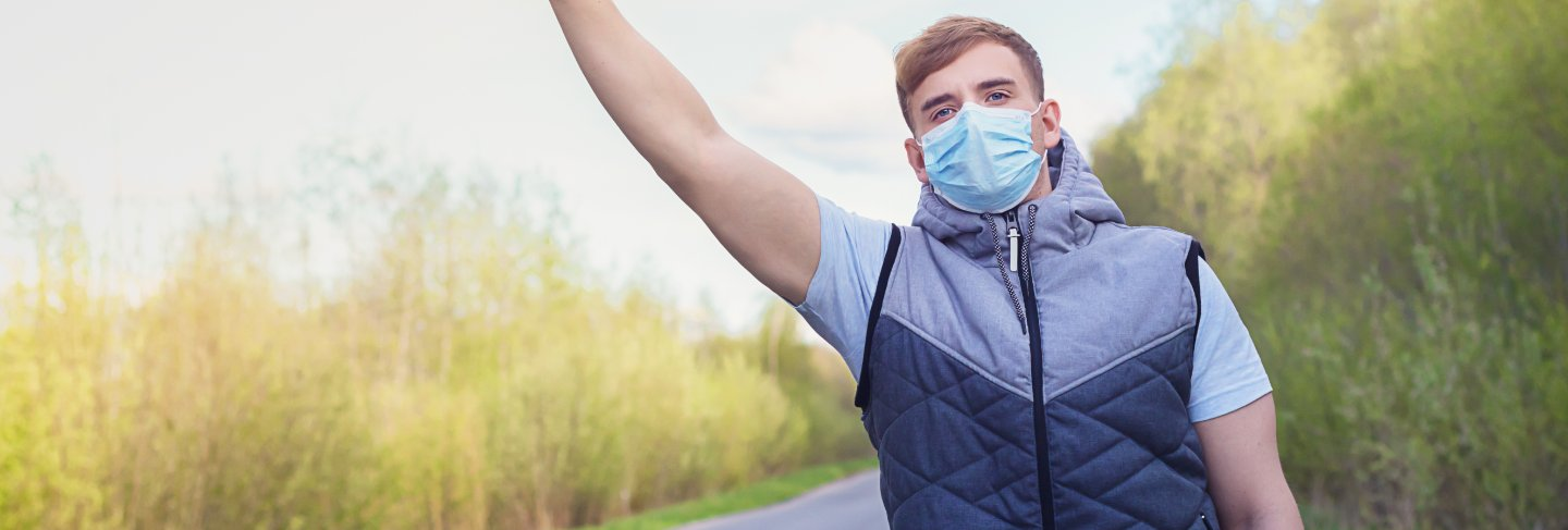 Guy in medical mask for prevention of coronavirus trying to stop auto, car.
