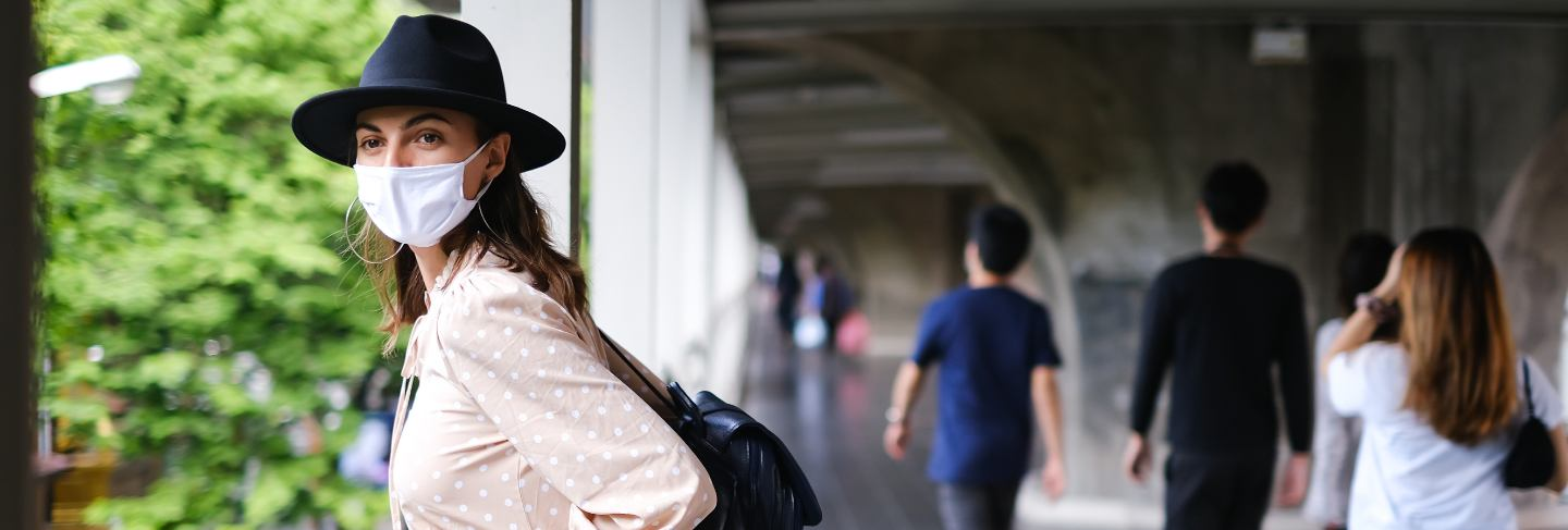 Caucasian woman walking on subway crossing in medical face mask while pandemia in bangkok city.
