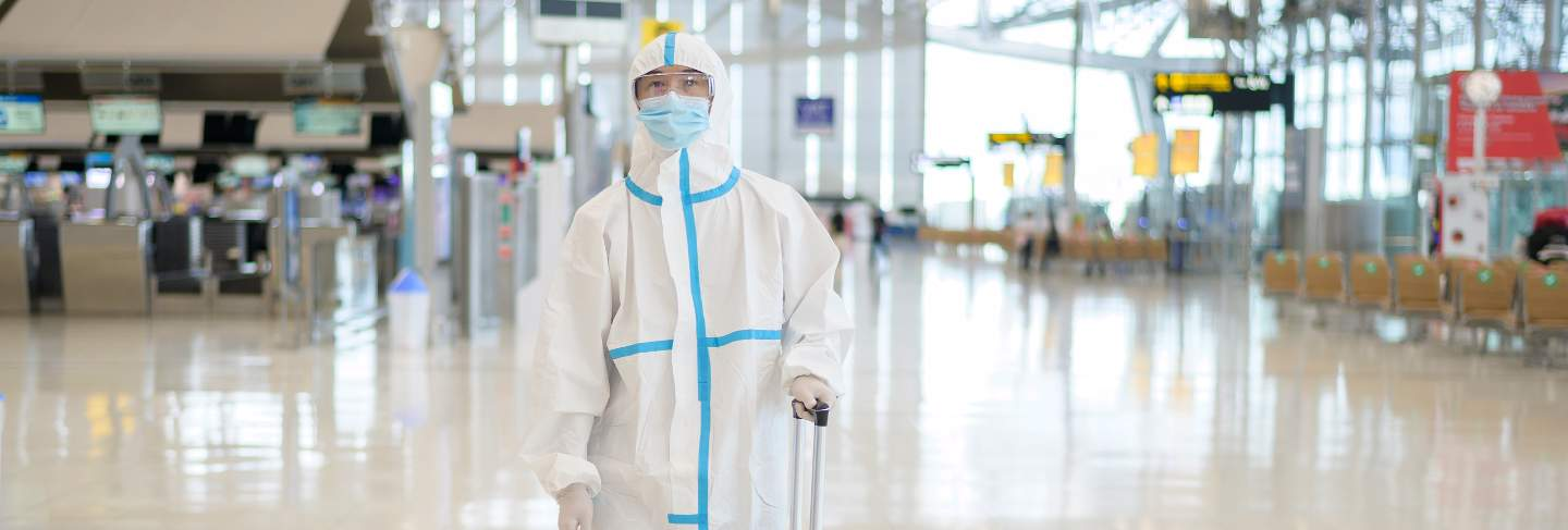 An asian man is wearing ppe suit in international airport , safety travel , covid-19 protection , social distancing concept