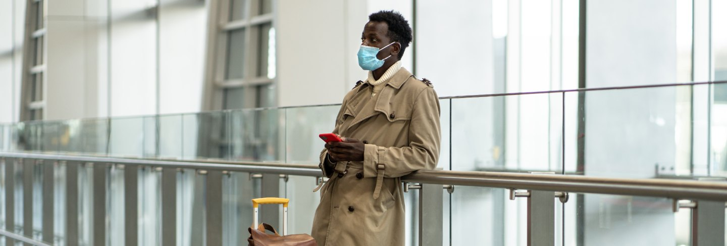 Afro-american traveler man with yellow suitcase stands in airport terminal, wear protective face mask to protect yourself from flu virus, pandemic covid-19, waiting for flight and boarding