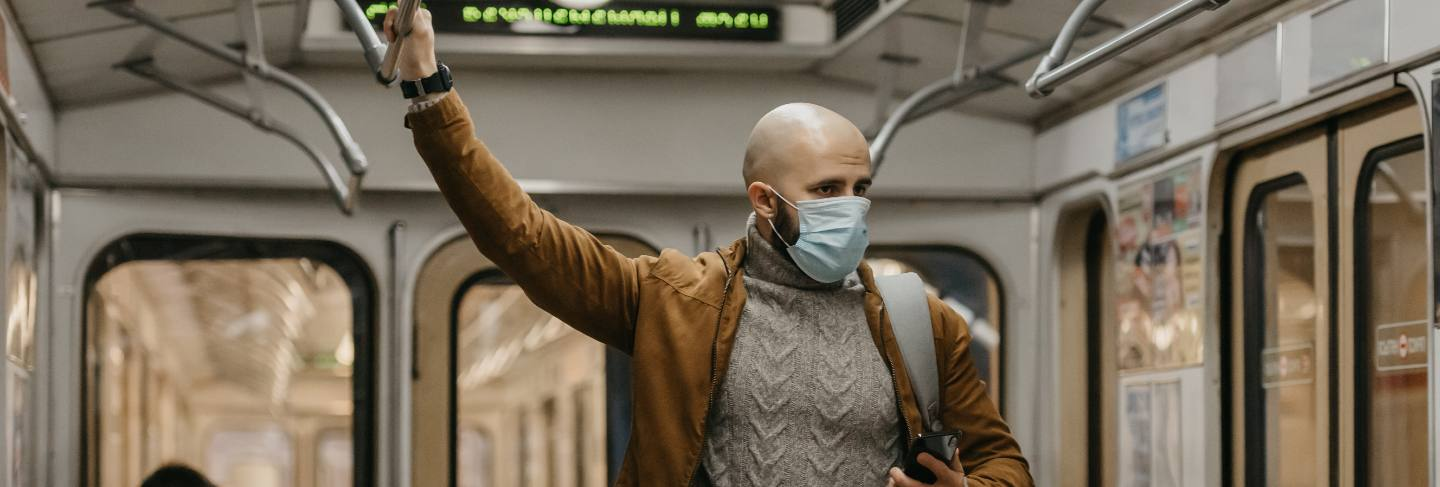 A man in a medical face mask at the subway station