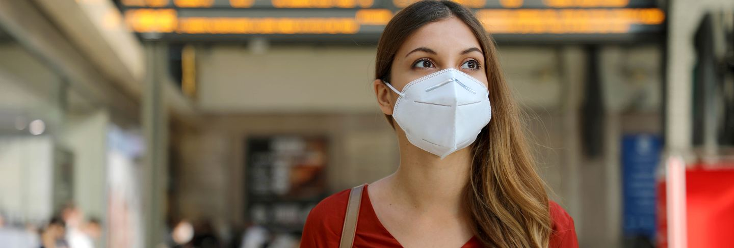 Traveler woman wearing kn95 ffp2 face mask at train station to protect from virus and smog.