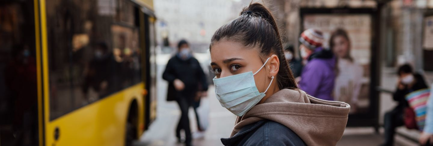 Young woman wearing surgical mask outdoor at bus stop in the street