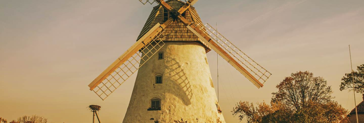 Restored old windmill on the mountainside. autumn sunny day.